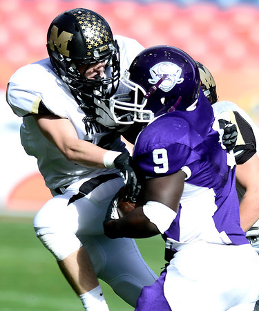 Monarch's Geoff Clary (left) stops Denver South's Trevonte Tasco (left) after a short gain during their 4A State Football Championship football game in Denver, Colorado December 1, 2012. BOULDER DAILY CAMERA/ Mark Leffingwell