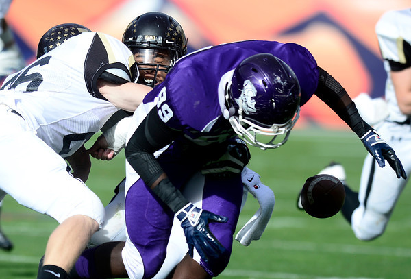 Monarch's Peter Mitchell (middle) and Jake Hummel (left) cause Denver South's Metise Moore (right) to fumble during their 4A State Football Championship football game in Denver, Colorado December 1, 2012. BOULDER DAILY CAMERA/ Mark Leffingwell