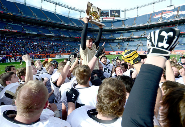 Monarch head coach Phil Bravo holds up the Championship Trophy while being cheered by his team after Monarch beat Denver South in the 4A State Football Championship football game in Denver, Colorado December 1, 2012. BOULDER DAILY CAMERA/ Mark Leffingwell