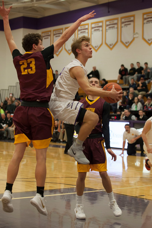 . Avon guard Ryan Maloy finds a way to maneuver past Avon Lake post Creed Bologna (23) to lay up his shot. Jen Forbus -- The Morning Journal