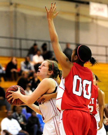 Fairview's Megan McCambridge (left) takes a shot under Denver East's Rhian Finley-Pond (right)  during their basketball game at Fairview High School in Boulder, Colorado December 14, 2012. BOULDER DAILY CAMERA/ Mark Leffingwell