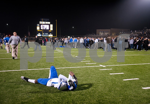 photo by Sarah A. Miller/Tyler Morning Telegraph  John Tyler's senior DeQuante Woods falls to the ground is disbelief after they lost to Guyer Friday night during the 4A Division 1 State Semifinal game at Midlothoian Stadium.