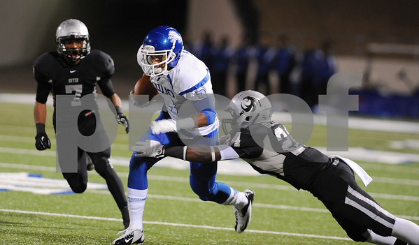 photo by Sarah A. Miller/Tyler Morning Telegraph  John Tyler's senior wide receiver Justice Liggins is stopped by Guyer's senior line back Terence Belton in the first half of their game Friday night at Midlothian Stadium.