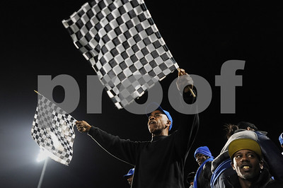 photo by Sarah A. Miller/Tyler Morning Telegraph  Joe Thompson of Tyler waves Nascar flags at the beginning of John Tyler's 4A Division 1 State Semifinal game Friday night at Midlothian Stadium. Thompson is a coach for the Little Cujos little league team in Tyler.