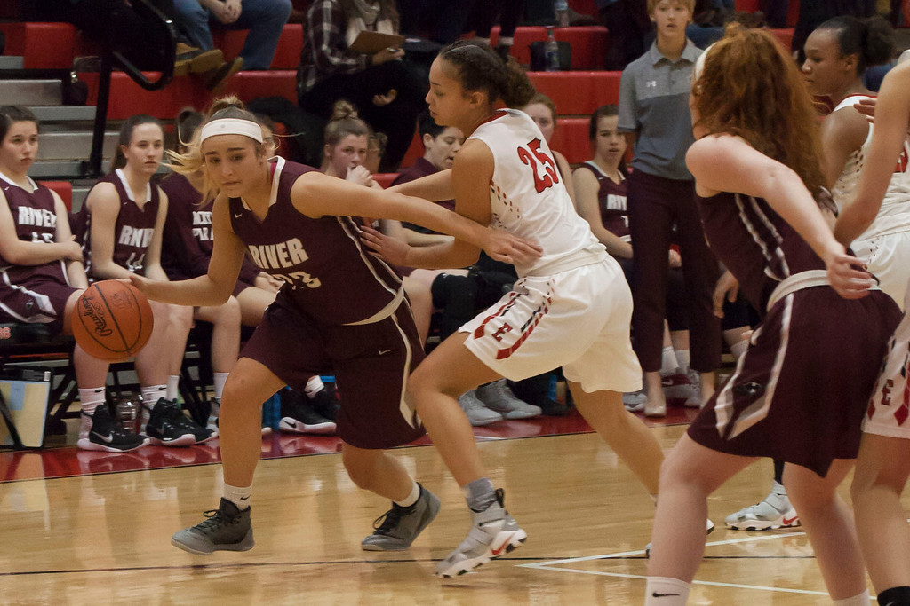 . Elyria\'s Myanna Hawkins sticks close to Rocky River\'s Hanna Chapman as she tries to drive the baseline. Jen Forbus -- The Morning Journal