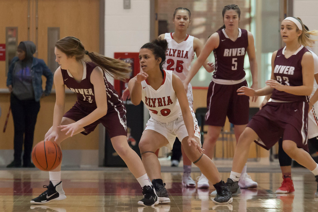 . Elyria\'s Tiffany Means stays close as River\'s Samantha Miller tries to find the basket. Jen Forbus -- The Morning Journal