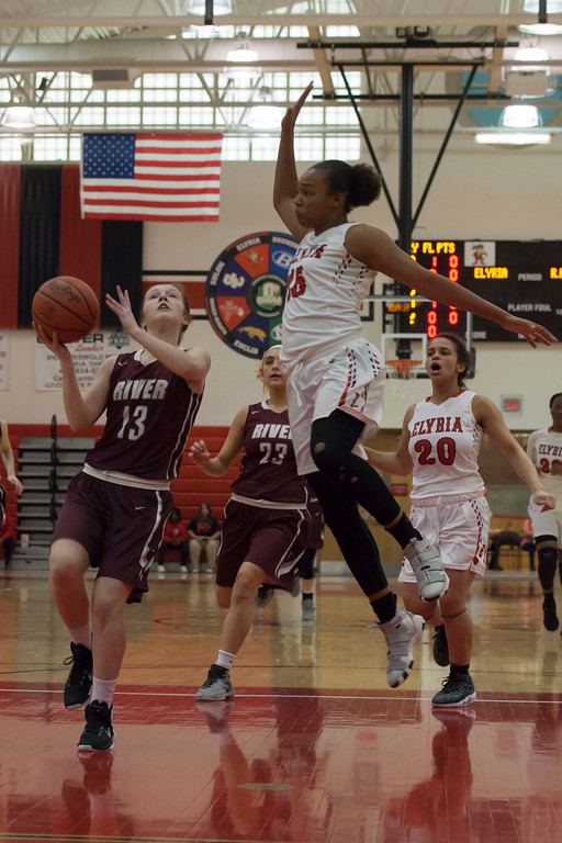 . Rocky River\'s Samantha Miller drives to the basket as Elyria\'s Chelsey Farris elevates to block her. Jen Forbus -- The Morning Journal