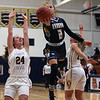 North Ridgeville's Izzy Geraci splits the defense of Danielle Stevens and Delaney Allan of Olmsted Falls for a underhand shot. Randy Meyers -- The Morning Journal
