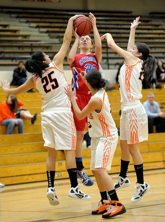 Surrounded by Lakewood's Valeria Miranda (left) Ariel Rosa (front middle) and Celina Quail (right) Centaurus' Anna Hubble is fouled by Valeria Miranda during their basketball game at Lakewood High School in Lakewood, ColoradoDecember 20, 2011. CAMERA/MARK LEFFINGWELL