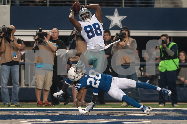 photo by Sarah A. Miller/ Tyler Morning Telegraph  Dallas Cowboy's wide receiver Dez Bryant (88) makes a catch in the end zone as Indianapolis Colts player Greg Toler (28) dives low Sunday Dec. 21, 2014 at AT&T Stadium in Arlington, Texas.