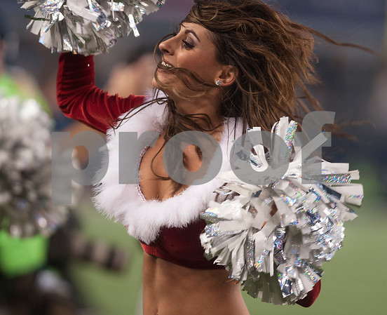 photo by Sarah A. Miller/ Tyler Morning Telegraph  A Dallas Cowboys cheerleader performs on the sideline in a Christmas themed uniform during their game Sunday Dec. 21, 2014 at AT&T Stadium in Arlington, Texas.