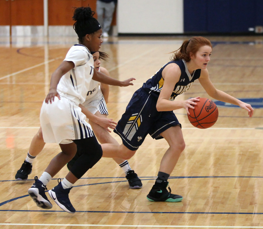 . North Ridgeville\'s Kolby Duke drives through a double team by Ashley Hisle and Normajanae Bohannon of Lorain during the first quarter. Randy Meyers -- The Morning Journal