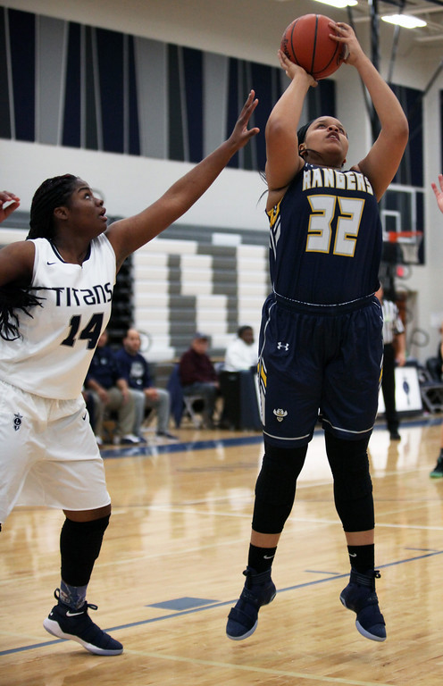 . North Ridgeville\'s Cianna Bright shoots and scores over Lorain\'s Nemaja\' Grant. Randy Meyers -- The Morning Journal