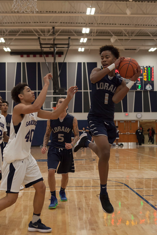 . Lorain forward Jordan Jackson (1) grabs the rebound as Sandusky forward Damon Green closes in. Jen Forbus -- The Morning Journal