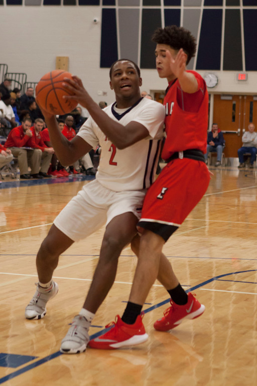 . Oberlin\'s Devan Yarber tries to make his way around Elyria\'s Caleb Rogers to get a shot at the basket. Jen Forbus -- The Morning Journal