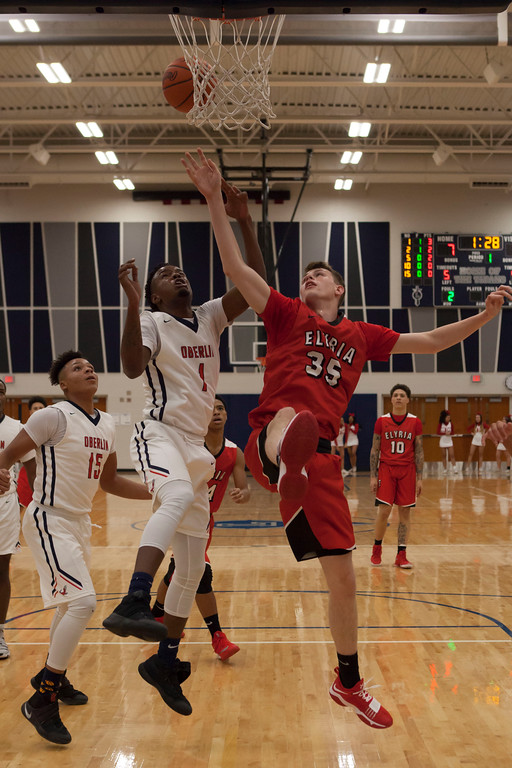 . Elyria\'s Justin Koepp and Oberlin\'s Justin Smith each try to snag the rebound. Jen Forbus -- The Morning Journal
