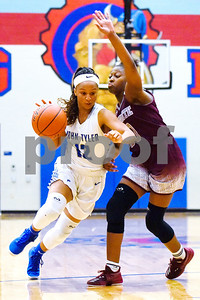 John Tyler's Zakiyah Jones (12) dribbles the ball as Mesquite's Alicia Bly (10) guards her during a high school basketball game at Boulter Middle School in Tyler, Texas, on Tuesday, Jan. 23, 2018. (Chelsea Purgahn/Tyler Morning Telegraph)