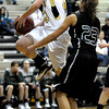 Monarch's Jordan Eisler (left) leaps past Fossil Ridge's Gabriella Smith for a shot during their basketball game at Monarch High School in Louisville, Colorado January 24, 2012.  CAMERA/MARK LEFFINGWELL