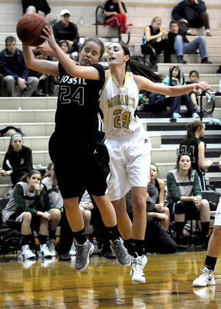 Monarch's Jac Malcolm-Peck (right) and Fossil Ridge's Haley Murphy go for a rebound during their basketball game at Monarch High School in Louisville, Colorado January 24, 2012.  CAMERA/MARK LEFFINGWELL