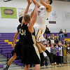 Boulder's Will Grubb (right) takes a shot over Rock Canyon's Jacob Cohn (left) and Jimmy Owsley (middle) during their basketball game at Boulder High School in Boulder, Colorado December 5, 2011. CAMERA/Mark Leffingwell