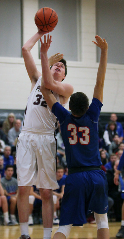 . Rocky River\'s Joey Coffman turns and shoots over Bay\'s Christian Dupps during the second quarter. Randy Meyers -- The Morning Journal