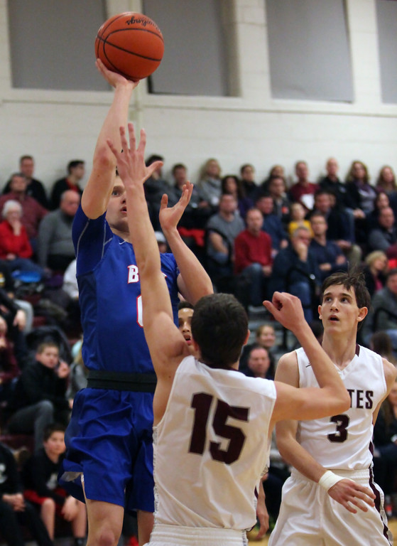 . Bay guard Max Showalter shoots and scores over Noah Steele of Rocky River during the first quarter. Randy Meyers -- The Morning Journal
