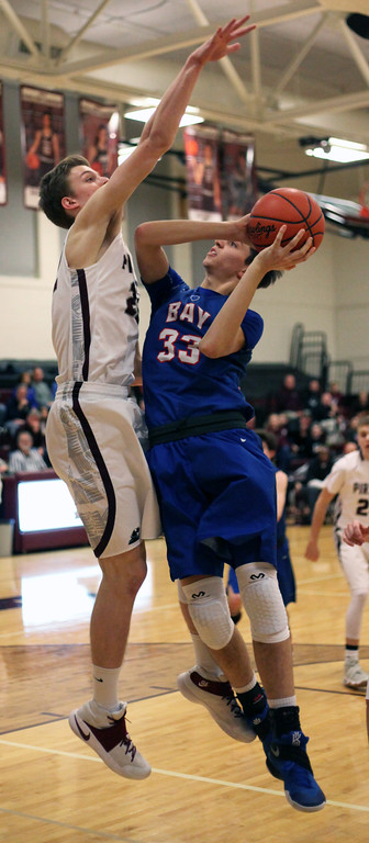 . Bay\'s Christian Dupps is fouled and scores over Joey Coffman of Rocky River during the third quarter. Randy Meyers -- The Morning Journal