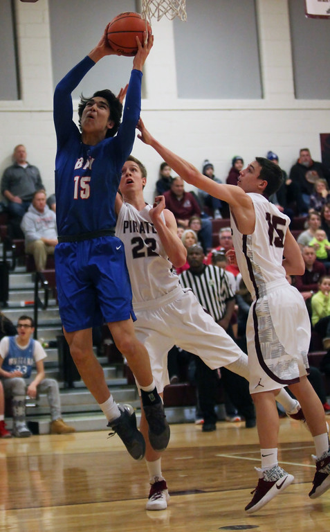 . Bay\'s RJ Sunahara shoots and scores over Zach Waite and Noah Steele of Rocky River during the first quarter. Randy Meyers -- The Morning Journal