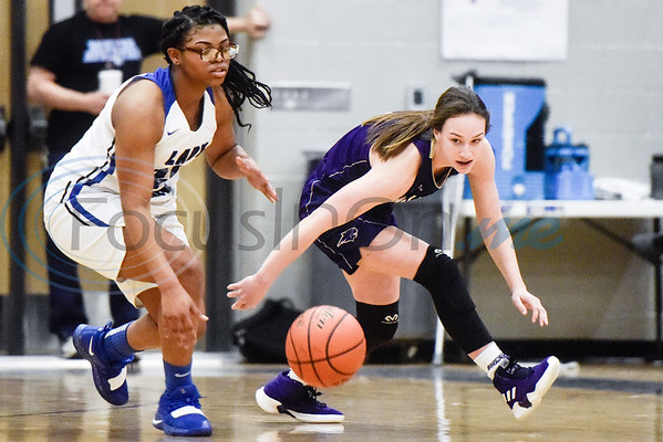 John Tyler's Destanie Bowie (22) and Hallsville's Mallory Pyle (2) reach for the ball during a high school basketball game at Boulter Middle School in Tyler, Texas, on Friday, Jan. 4, 2019. (Chelsea Purgahn/Tyler Morning Telegraph)