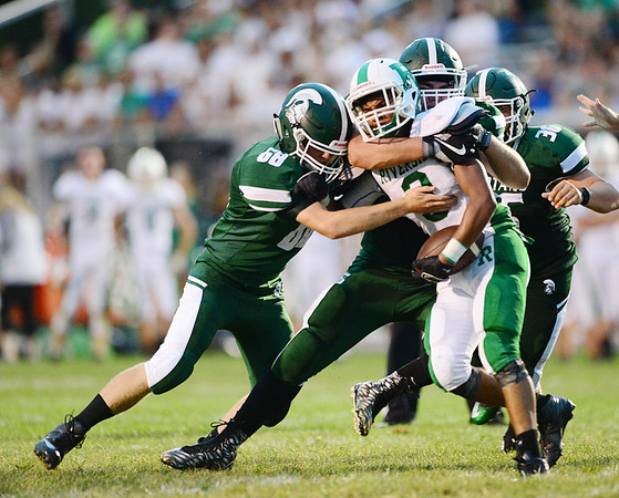 From left, Laurel's Mike Seth, Josh Wargo and Dominic Wade take down a Riverside ball carrier.