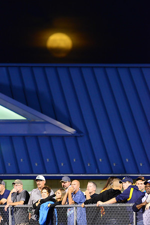 Wilmington fans watch from the sidelines as a harvest moon rises over the stadium Friday night.