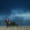 A Hurricane fan stands alone at the top of the stadium as clouds roll behind him.