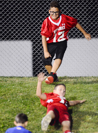 From top, Santino Soubra, 8 and team mate Dante Canciello, 8 take turns sliding down the hill at the football game Friday night.