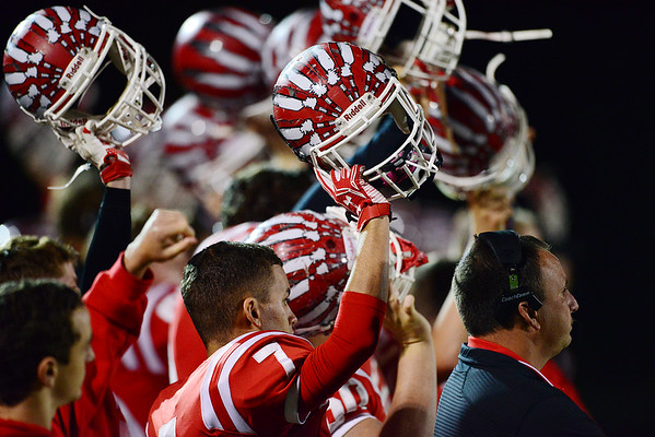Mohawk players on the sidelines lift their helmets in solidarity during the return kick.
