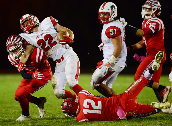 From left, Mohawk's Nathan McCutcheon and Dmitry Pendro take down a Freedom ball carrier.