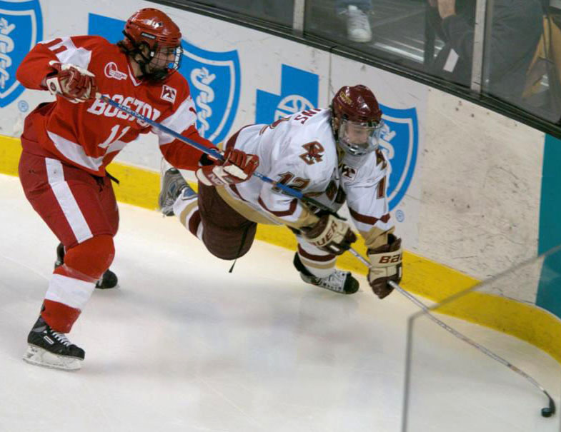 BC's Chris Collins reaches for the puck as BU's Dan Spang tries to hook him