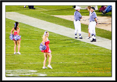 Standford cheerleaders performing while the referees chat.