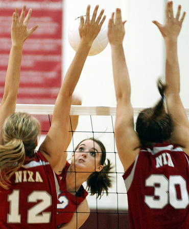 Globe/T. Rob Brown<br /> Webb City's (12) Kelsey Erwin makes a kill attempt against Nixa's defense including Kyrie Hopkins (12) and Kylie Heim (30) in the second game during the final match of the District 12 Volleyball Tournament Wednesday night, Oct. 25, 2006, at Joplin High School.<br /> Section: Sports