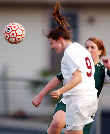 Herald/T. Rob Brown<br /> Joplin's (9) uses her head to direct the ball away from a Springfield Catholic player Wednesday evening, March 29, 2006, at Joplin High School's soccer field.<br /> Section: Sports