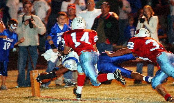 Globe/T. Rob Brown<br /> Carthage's Caleb Sanders (2) scores a touchdown at the corner as Webb City defenders Brad Workman (14) and Zac Anderson (33) attempt to stop him during Wednesday night's game, Nov. 8, 2006, at Webb City.<br /> Section: Sports