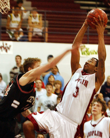 Globe/T. Rob Brown<br /> Joplin's Damian Colbert (3) leaps up to shoot two over Springfield Central defender Zach Case (34) Tuesday night, Feb. 21, 2006, at Joplin High School during the Class 5 District 12 basketball tournament.<br /> Section: Sports Story: Michael Davison