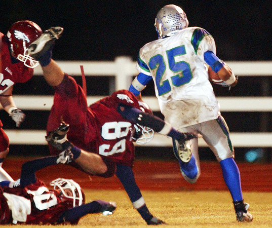 Globe/T. Rob Brown<br /> Joplin High School's Chris Delzell (89) leaps after South Blue Springs ball carrier Shane Simpson (25) during Friday night's game, Oct. 27, 2006, at Junge Stadium.<br /> Section: Sports