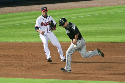 Marlins LF Cody Ross narrowly misses being hit by a line drive as Braves 3B Chipper Jones looks on.