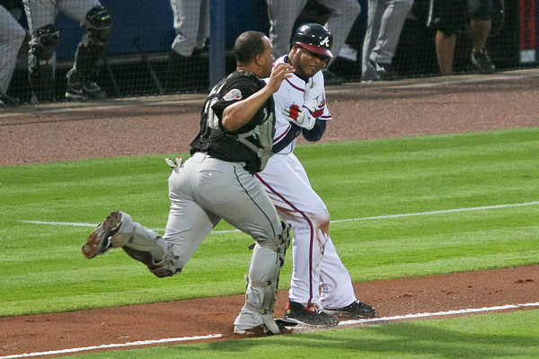 After a poor attempt at a bunt by John Smoltz, Andruw Jones is caught trying to steal home by Marlins catcher Miguel Olivo and pitcher Kim.