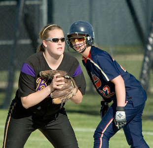 Belvidere North High School's Taelor Pipkin (right) looks for a chance to steal second base while Belvidere High School's first baseman Amanda Hartzell watches the pitch