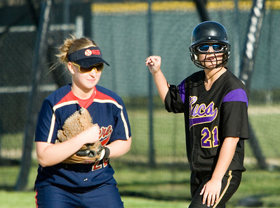 Belvidere High School's Brittany Denny (right) waits for a chance to run to second base as Belvidere North High School's Taelor Pipkin (left) watches a pitch.
