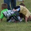 A three kid pileup om the soccer field