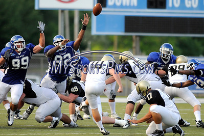 Bryant College's Christopher Bird kicks a field goal while under pressure from Central Connecticut State University's Roberto Rodriguez (99) and Danny Rodriguez on Saturday afternoon to make it 21-13, CCSU at the half.