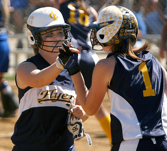Franklin County baserunner Rachel Hall, left, is congratulated by teammate Emily Hampton after scoring a run during the Flyers' game against Estill County Friday morning during the first round of the KHSAA Fast Pitch Softball State Tournament in Owensboro, KY. Franklin County won 4-0, advancing into a second-round matchup against Allen County-Scottsville in the double-elimination tournament.