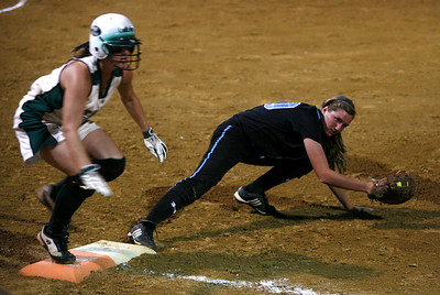 Owensboro Catholic baserunner Carly Kaelin steps on first as Mercy first baseman Morgan Ellington picks up the ball during the KHSAA Fast Pitch Softball Championship Game Saturday night in Owensboro. Kaelin was ruled safe on the play after being called out initially. Owensboro Catholic won the game 12-2.